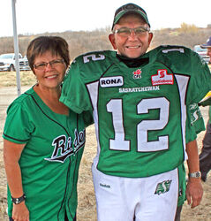 Carol and George Stuart proudly pose with their Rider green at the Grey Cup 100 Tour in Minnedosa.