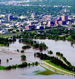 Flooded First Street North and Dinsdale Park, with the Brandon downtown skyline behind.