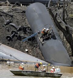 FILE - This May 1, 2014 file photo shows the site where several CSX tanker cars carrying crude oil derailed and caught fire along the James River near downtown Lynchburg, Va. U.S. Railroads forced to turn over details on crude oil shipments are asking states to sign agreements not to disclose the information but some officials are refusing, saying it should be public. Federal officials last month ordered railroads to make the disclosures following a string of fiery tank car accidents in North Dakota, Alabama, Virginia, Quebec and elsewhere. (AP Photo/Steve Helber, file)