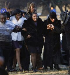 FILE - In this Feb. 9, 2013 file photo, Cleopatra Pendleton, center, is escorted to the gravesite of her daughter, 15-year-old Hadiya Pendleton, during funeral services at the Cedar Park Cemetery in Calumet Park, Ill. Pendleton was was shot and killed Jan. 29, 2013 in a park during a gang dispute she had nothing to do with about a mile from President Barack Obama's Chicago home. Since Pendleton's death a year ago, homicide and other violent crimes have fallen sharply as police and the city have changes strategies. (AP Photo/Charles Rex Arbogast, File)