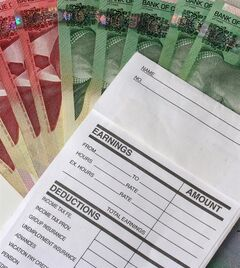 Cash and payroll slips are shown. THE CANADIAN PRESS/Richard Plume