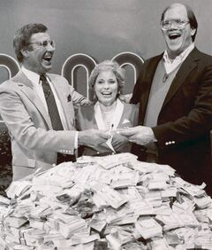 File-This Jan. 16, 1986. file photo shows host Jim Lange, left, congratulating Connie and Steve Rutenbar of Mission Viejo, Calif., after they won $1 million on the TV show