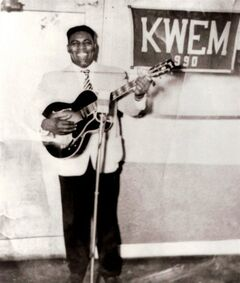 In this undated photo provided by Mid-South Community College in West Memphis, Ark., blues singer Howlin' Wolf holds a guitar near a banner for radio station KWEM. The station, now owned by the college, that began broadcasting in West Memphis in 1947 and lasted until 1960 is being re-launched this week on the Internet. Plans are for a return to the air as an FM broadcast in August 2014. (AP Photo/Mid-South Community College)