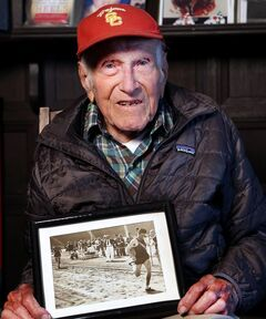 This Jan. 21, 2014 photo provided by USC Dornsife College of Letters, Arts and Sciences, Louis Zamperini displays one of his photographs as a student and sprinter, at his Los Angeles home. Zamperini, a U.S. Olympic distance runner and World War II veteran who survived 47 days on a raft in the Pacific after his bomber crashed, then endured two years in Japanese prison camps, died Wednesday, July 2, 2014, according to Universal Pictures studio spokesman Michael Moses. He was 97. (AP Photo/Matt Meindl/USC Dornsife College of Letters, Arts and Sciences)
