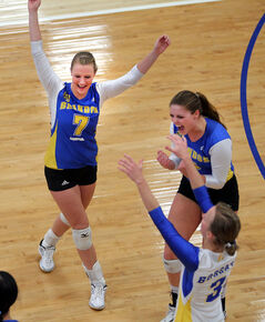 Brandon's Kellie Baker (top left), Shanlee McLennan and Donata Huebert celebrate a point over Trinity Western during university women's volleyball action on Saturday.