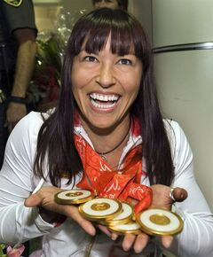 Chantal Petitclerc, winner of five gold medals at the 2008 Paralympics in Beijing, shows her medals as she arrives at Trudeau airport in Montreal Friday, Sept. 19, 2008. Petitclerc is Canada's chef de mission at the upcoming Commonweath Games in Glasgow, Scotland. THE CANADIAN PRESS/Ryan Remiorz