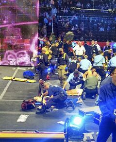 FILE - In this May 4, 2014 file photo provided by Rosa Viveiros, first responders work at the center ring after a platform collapsed during an aerial hair-hanging stunt at the Ringling Brothers and Barnum and Bailey Circus in Providence, R.I. Seven of the eight hair-hanging acrobats who fell to the Dunkin' Donuts Center floor during the stunt have hired a Chicago-based law firm to represent them, the firm announced Monday, June 16, 2014. (AP Photo/Rosa Viveiros, File) MANDATORY CREDIT