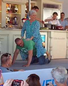 Paula Deen gets a ride across stage from Food Network star Robert Irvine during a cooking demo at the South Beach Wine and Food Festival in Miami, Fla., Sunday, Feb. 23, 2014. Deen continued maneuvering for a comeback Sunday, turning a beachside cooking demonstration into a public apology for the racist comments that decimated her career last year. (AP Photo/J.M. Hirsch)