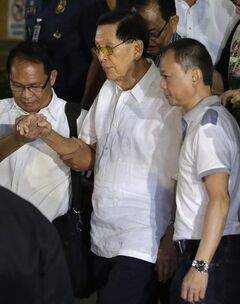 Former Senate President Juan Ponce Enrile, center, is helped to a waiting ambulance after undergoing processing at the Philippine National Police upon his surrender on corruption charges Friday, July 4, 2014 at Camp Crame at suburban Quezon city, northeast of Manila, Philippines. Enrile, 90, surrendered Friday to face a charge of large-scale corruption, the most prominent of three top politicians to fall in a government anti-graft crackdown in recent weeks. (AP Photo/Bullit Marquez)