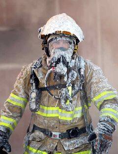 Ice clings to the equipment on a firefighter battling the blaze at a set of businesses on Pacific Avenue near Second Street on Monday.