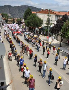 Several hundred members of the Union of Turkish Youth wear miner's helmets during a march to commemorate the Soma coal mine victims, in Amasya, Turkey, Sunday, May 18, 2014. Eighteen people, including mining company executives, have been detained as Turkish officials investigate the mining disaster that killed 301 people, a domestic news agency reported Sunday. (AP Photo/Emre Tazegul)