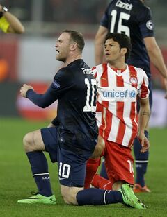 Manchester United's Wayne Rooney reacts to the referee's decision as Nelson Valdez looks on during their Champions League, round of 16, first leg soccer match at Georgios Karaiskakis stadium, in Piraeus port, near Athens, on Tuesday, Feb. 25, 2014. Olympiakos won 2-0. (AP Photo/Thanassis Stavrakis)