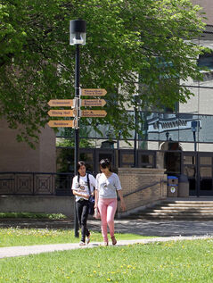 In this June photo, a pair of students take a walk on the Brandon University campus. Figures show last year, 101 BU employees earned more than $100,000.
