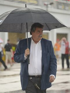 Mike Helton, president of NASCAR walks through the garages during a rain shower prior to the Sprint Cup series auto race at Daytona International Speedway in Daytona Beach, Fla., Saturday, July 5, 2014. (AP Photo/Phelan M. Ebenhack)