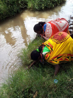 "Two of ""the Mommas"" gather water that they and the students would carry back to one of Maasai homes."