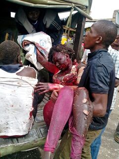 EDITORS NOTE GRAPHIC CONTENT - An injured woman is carried to a small truck in Jos, Nigeria, Tuesday, May 20, 2014. Two explosions ripped through a bustling bus terminal and market frequented by thousands of people in Nigeria's central city of Jos on Tuesday afternoon, and police said there are an unknown number of casualties. The blasts could be heard miles away and clouds of black smoke rose above the city as firefighters and rescue workers struggled to reach the area as thousands of people fled. (AP Photo/Stefanos Foundation)