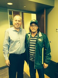 Connor Croken, right, poses for a photo with Eskimos President and CEO Len Rhodes in Edmonton on Friday, July 25, 2014. The Edmonton Eskimos say a 20-year-old man has won the largest 50-50 draw in the football club's history. The CFL team says Connor Croken of Edmonton presented the winning ticket worth $348,534 when the Eskimos office opened this morning. THE CANADIAN PRESS/HO - Edmonton Eskimos
