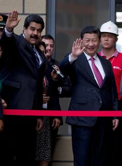 China's President Xi Jinping, right, and Venezuela's President Nicolas Maduro greet supporters during a visit to an apartment complex built under an agreement between China and Venezuela in Caracas, Venezuela, Monday, July 21, 2014. Xi Jinping is in Venezuela for a two day official visit. (AP Photo/Fernando Llano)
