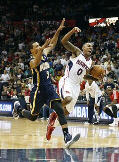 Atlanta Hawks guard Jeff Teague (0) trips as he breaks for the goal against Indiana Pacers guard George Hill (3) in the second half of Game 3 of an NBA basketball first-round playoff series on Thursday, April 24, 2014, in Atlanta. The Hawks won 98-85. (AP Photo/John Bazemore)