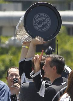 In this photo taken on Monday, June 16, 2014, Los Angeles Mayor Eric Garcetti, right, celebrates with Los Angeles Kings team members holding up the Stanley Cup trophy while riding in a parade downtown Los Angeles. Mayor Garcetti used the F-bomb in declaring it a big day for LA, bringing 19,000 hockey fans to their feet, lighting up the Twitterverse in delight and, oh yeah, leaving some folks scratching their heads, wondering just what the heck the normally soft-spoken elected official was thinking. (AP Photo/Nick Ut)
