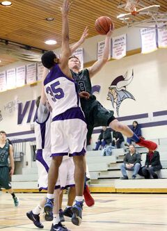 Brant Bosiak of the Dauphin Clippers leaps for a shot against Daven Pascal of the Vincent Massey Vikings at the Brandon Sun Spartan Invitational boys basketball tournament Friday.