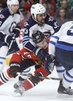 Winnipeg Jets defenseman Dustin Byfuglien (33) takes Chicago Blackhawks center Jonathan Toews (19) down after Toews' shot on goal during the second period of an NHL hockey game Sunday, Jan. 26, 2014, in Chicago. (AP Photo/Charles Rex Arbogast)