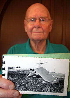 Len Fisher, 91, holds up a photo of the plane he crashed while spraying a field near Neepawa on June 23, 1953. Fisher is filing a claim with the Workers Compensation Board almost 60 years after the accident for expenses incurred during the eight months he spent in Winnipeg General Hospital recovering.