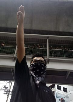 In this Sunday, June 1, 2014 photo, an anti-coup protester gives a three-finger salute as soldiers keep eyes on him from an elevated walkway near a rally site in central Bangkok, Thailand. Thailand's military rulers say they are monitoring the new form of silent resistance to the coup - borrowed from