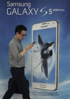 A man walks by an advertisement of Samsung Electronics' Galaxy S5 smartphone at the company's showroom in Seoul, South Korea, Thursday, July 31, 2014. Samsung Electronics Co. reported a bigger-than-expected fall in second quarter profit on Thursday and said it was uncertain if earnings from its handset business would improve in the current quarter.(AP Photo/Ahn Young-joon)