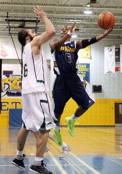 Ilarion Bonhomme (right) of the Brandon Bobcats leaps for a shot as Paul Gareau of the Regina Cougars goes for a block during men's university basketball action on Saturday.
