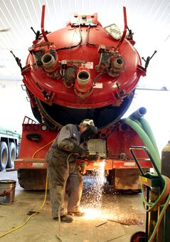 Tom Wilson, a mechanic with Taylor Oilfield Services works to replace a float inside a vacuum truck, at the Melita-area business.