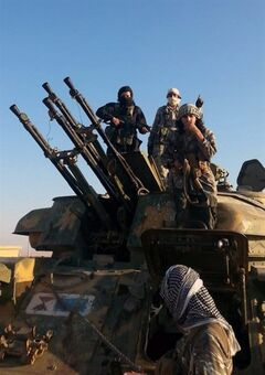 This image posted by the Raqqa Media Center shows fighters from the Islamic State group on top of a military vehicle with anti-aircraft guns in Raqqa, Syria, Thursday, Aug 7, 2014. The Islamic State militants seized the Brigade 93 base overnight after days of heavy fighting, according to the Syrian Observatory for Human Rights and the Raqqa Media Center, an activist collective. The base lies some 40 miles (60 kilometers) from the provincial capital of Raqqa, a stronghold for the Islamic State group. (AP Photo/Raqqa Media Center)