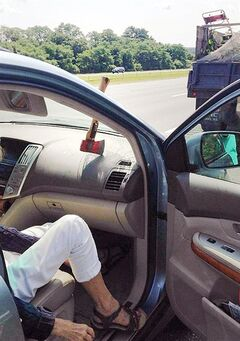 In a photo provided by Massachusetts State Police, an ax head rests on the dashboard with the handle stuck in the windshield of a motorist's car after falling off a landscaper's truck on Route 95 in Topsfield, Mass., Wednesday July 30, 2014. Police said the car's passenger was