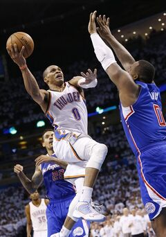 Oklahoma City Thunder guard Russell Westbrook, center, goes up for a shot in front of Los Angeles Clippers forward Glen Davis, right, in the fourth quarter of Game 5 of the Western Conference semifinal NBA basketball playoff series in Oklahoma City, Tuesday, May 13, 2014. Oklahoma City won 105-104. (AP Photo)