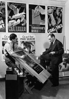 John Grierson, right, the first commissioner (1939-1945) of the National Film Board of Canada, looks at move posters in this handout photo from 1944. The National Film Board is celebrating its 75th anniversary this year with a new documentary about its early years between 1939 and 1945. Called