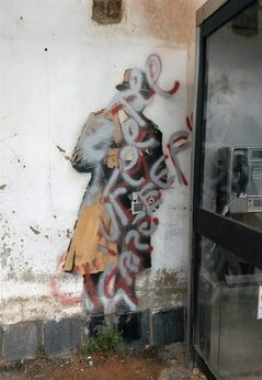 A view of the Banksy mural which targets the issue of Government surveillance with silver and red paint sprayed over it, Cheltenham, England, Friday, Aug. 1, 2014. A mural by street artist Banksy that sparked a local preservation campaign has been defaced.