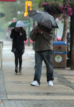Pedestrians make their way along Rosser Avenue under the protection of their umbrellas on Thursday.