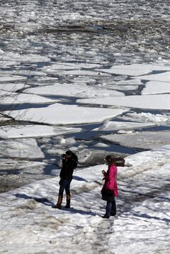 Visitors take pictures of an ice filled Chicago River Wednesday, Feb. 19, 2014, in downtown Chicago. Weeks of subfreezing weather are giving way, at least briefly, to temperatures in the 50s, putting cities on guard for flooding, roof collapses and clogged storm drains. (AP Photo/Kiichiro Sato)