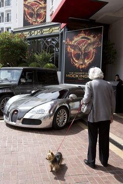 "In this photo taken on Monday, May 12, 2014, a woman walking her dog looks at a Bugatti car and a poster for the ""Hunger Games, Mockingjay: Part 1"" at a hotel in Cannes, France. (AP Photo/Virginia Mayo)"