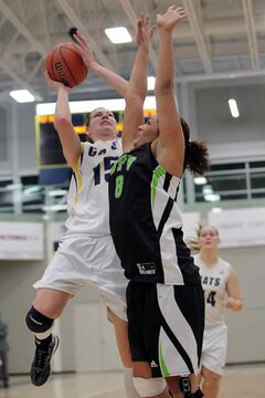 Jaynell Gillett, left, of the Brandon University Bobcats leaps for a shot as Shayna Litman of the University of the Fraser Valley Cascades defends at BU's Healthy Living Centre Friday.