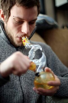 Medicinal marijuana user Doug Affleck smokes marijuana from a bong in Ridge's residence.