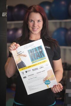 Fitness Quest trainer Lylas Leona Poulton holds a poster for her gym's Weight Loss War challenge which begins in the new year.