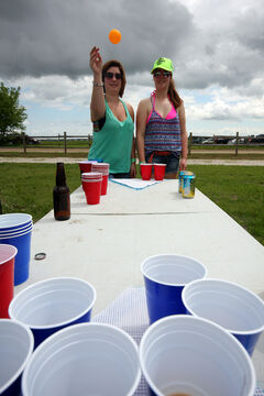 Brandon's Kirsty Fischer takes dead aim at a blue cup while playing beer pong at Dauphin's Countryfest on Thursday. Fischer, who has been coming to the festival for four years, is playing with her friend Michaela Kilbride.