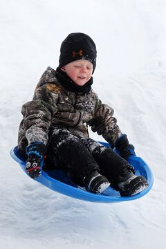 Jaixon Ledoux sails off a jump while sledding in Wasagaming on Saturday. Winter Adventure Weekend events included snowshoeing, Winter Olympics, skating, maple syrup rolling and a variety of other activities.