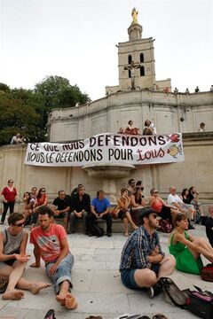 Part-time and temporary arts workers, striking artists and theater personnel, known as 'intermittents', attend a general assembly, in Avignon, France, Friday, July 4, 2014. Organizers of one of Europe's premier theater festivals are cancelling some shows amid a protest movement by cultural workers over changes to their off-season unemployment benefits. The director of the Festival d'Avignon, Olivier Py, told journalists in Avignon that two plays scheduled for Friday's opening night have been called off. The CGT union announced a strike, but it's unclear how many workers will take part. Banner reads :