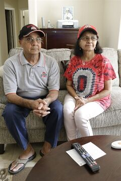 In this June 25, 2014 photo Arun, left, and Usha Pancholi, recent transplants from Colombus, Ohio and big Ohio State fans, watch TV at their home at ShantiNiketan, a retirement community for people from India, in Tavares, Fla. ShantiNiketan is one of a growing number of niche retirement communities aimed at people of specific ethnic backgrounds, hobbies or collegiate allegiances. (AP Photo/John Raoux)