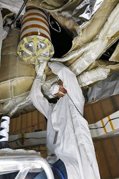In this undated photo provided by NASA, an engineer works on the Parachute Deployment Device of the Low Density Supersonic Decelerator (LDSD) test vehicle in this image taken at the Missile Assembly Building at the US Navy's Pacific Missile Range Facility at Kekaha on the island of Kaua'i in Hawaii. From high altitudes above Earth, the vehicle will test two devices for landing future heavy payloads on Mars. The U.S. space agency is deciding its next move after it lost the chance to launch the vehicle into the Earth's atmosphere because of unfavorable wind conditions. The mission is designed to test technology that could be used on Mars. (AP Photo/NASA)