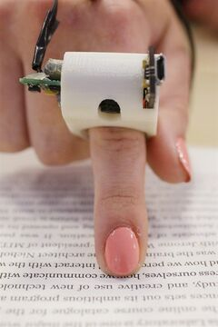 In this June 26, 2014 photo, a model wears a FingerReader ring at the Massachusetts Institute of Technology's Media Lab in Cambridge, Mass. Researchers designed and developed the instrument, which enables people with visual disabilities to read text printed on paper or electronic devices. (AP Photo Stephan Savoia)