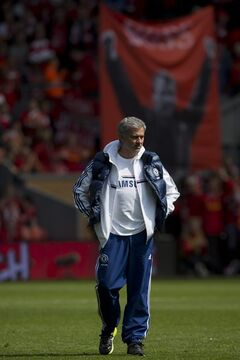 Chelsea's manager Jose Mourinho watches his team warm up in front of a banner of Liverpool's manager manager Brendan Rodgers before their English Premier League soccer match at Anfield Stadium, Liverpool, England, Sunday April 27, 2014. (AP Photo/Jon Super)