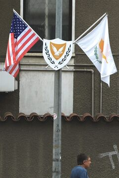 A man passes by an electricity column with a US flag, left, and Cypriot flag displayed, in divided capital Nicosia, Cyprus, Tuesday, May 20, 2014. US Vice President Joe Biden arrives in Cyprus Wednesday for an official, three-day visit to the ethnically divided island. Energy prospects in the east Mediterranean, the situation in Ukraine and talks to reunify Cyprus will top Biden's agenda, who is the most senior American official to visit the island in 52 years. (AP Photo/Petros Karadjias)